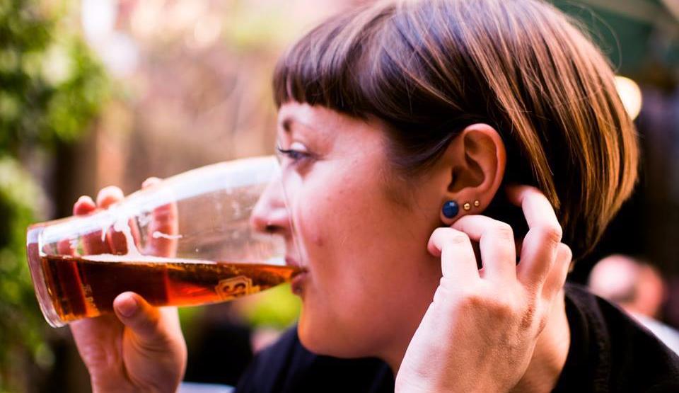 A woman drinking ale in a pub in London